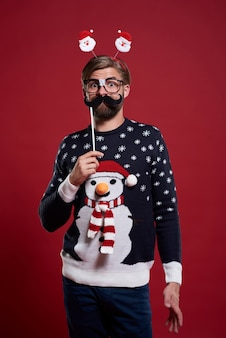 Lustiger mann mit schnurrbartmaske gekleidet in weihnachtskleidung