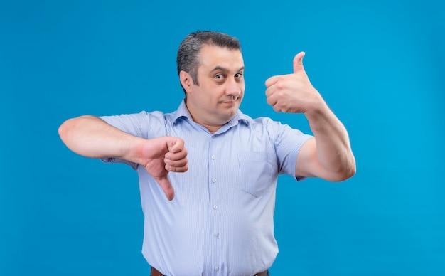 Lustiger mann mittleren alters im blau gestreiften hemd, das daumen hoch und daumen runter auf einem blauen raum zeigt