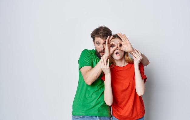 Lustiger mann und frau in mehrfarbigen t-shirts emotionen hand gestikuliert freundschaft.