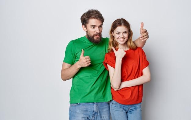 Lustiger mann und frau in mehrfarbigen t-shirts emotionen handgesten