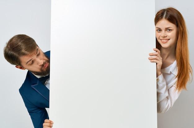 Lustiger mann und frau mit weißem mockup-plakat-werbeschild mit weißem hintergrund
