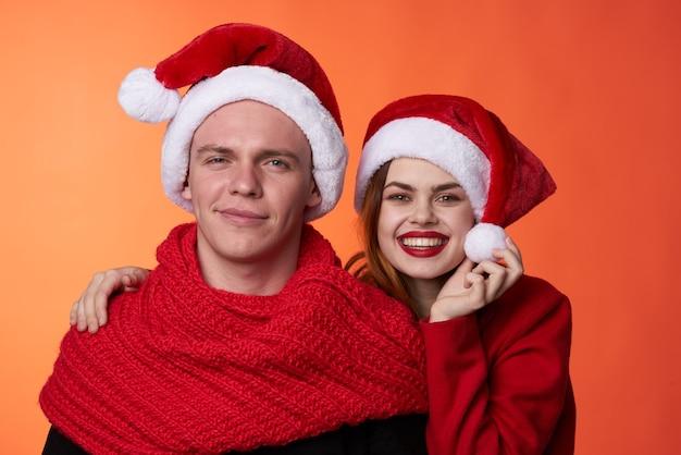 Lustiger mann und frau weihnachten santa hut freundschaft roten hintergrund. foto in hoher qualität
