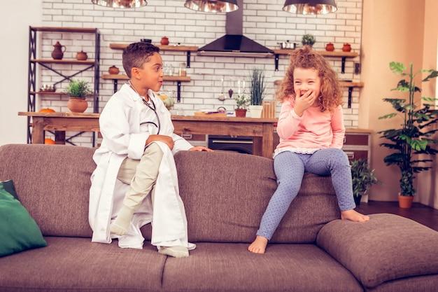 Lustiger moment. erfreuter internationaler junge, der die beine kreuzt, während er auf dem sofa sitzt und seinen freund ansieht?