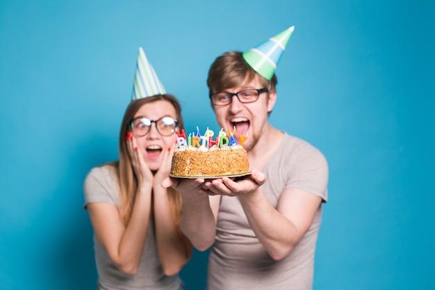 Lustiger nerd mann und frau tragen feiertagsmützen und gläser, die geburtstagstorte mit kerzen halten