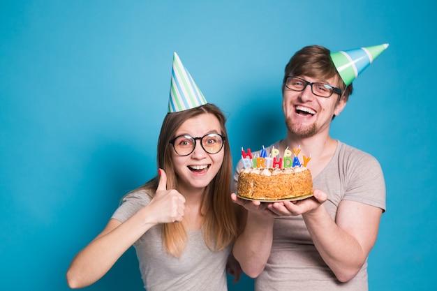 Lustiger nerd mann und frau tragen feiertagsmützen und gläser, die geburtstagstorte mit kerzen über blauer wand halten