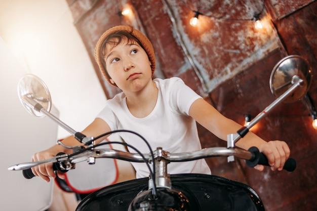 Lustiger netter tweenjunge im hut und im weißen t-shirt auf motorrad stellt sich als erwachsener mann dar und kühlt ab