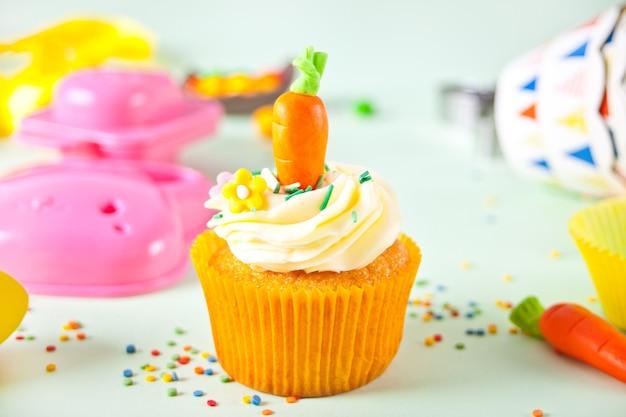 Lustiger oster-cupcake mit süßigkeiten-karotte. osterfeier festlicher tisch.