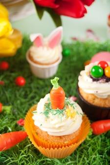 Lustiger oster-cupcake mit süßigkeits-karotte