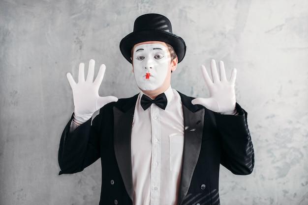 Lustiger pantomime-schauspieler mit make-up-maske. pantomime in anzug, handschuhen und hut.