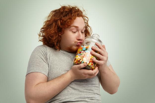 Lustiger praller junger kaukasischer mann mit lockigem ingwerhaar, der glasglas süßigkeiten und marmeladen küsst, es sanft zu herzen umklammernd. fettleibigkeit, völlerei, essen, ernährung und ungesundes lifestyle-konzept
