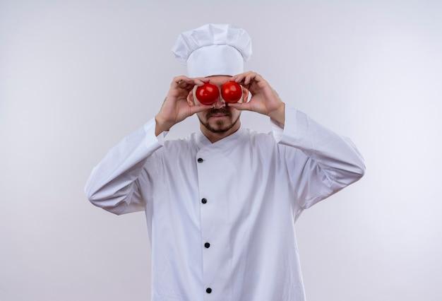 Lustiger professioneller männlicher koch kocht in der weißen uniform und im kochhut, der augen mit tomaten bedeckt, die über weißem hintergrund stehen