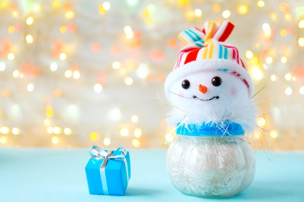 Lustiger schneemann des spielzeugs in einem farbigen hut und einer blauen geschenkbox mit band auf hellem hintergrund mit bokeh
