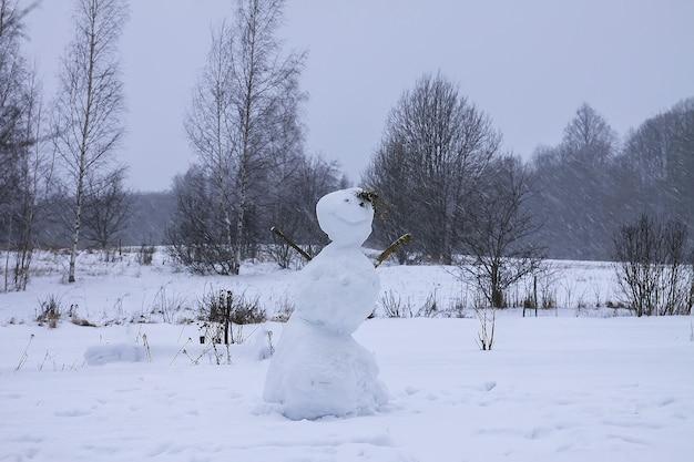 Lustiger schneemann von kindern auf schneebedecktem ländlichem feld gemacht