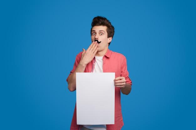 Lustiger schockierter mann, der weißes papier hält