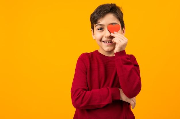 Lustiger schöner kaukasischer junge mit einer papierkarte in form eines herzens für valentinstag auf einem orangefarbenen hintergrund.