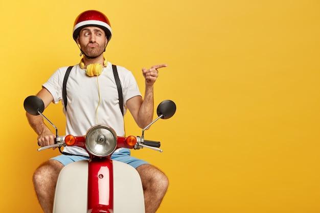 Lustiger schöner männlicher fahrer auf roller mit rotem helm