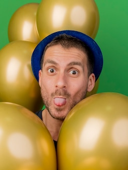 Lustiger schöner mann, der blauen parteihut trägt, steckt zungenständer mit heliumballons isoliert auf grüner wand aus