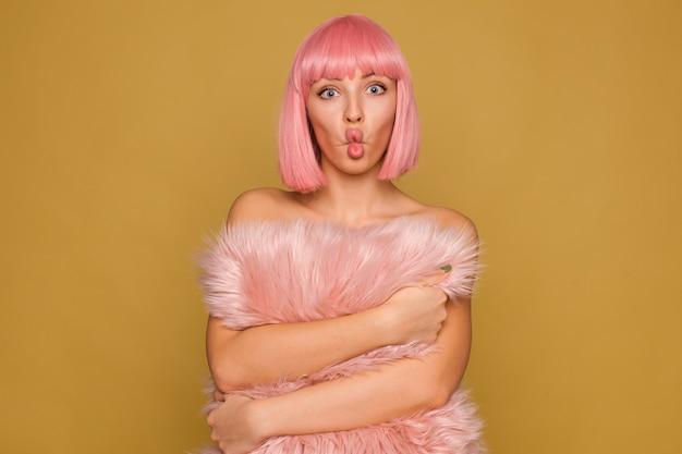 Lustiger schuss der jungen attraktiven rosa behaarten frau mit dem kurzen trendigen haarschnitt, der gesichter macht, während sie über senfwand mit niedlichem pelzigem kissen in ihren händen aufwirft