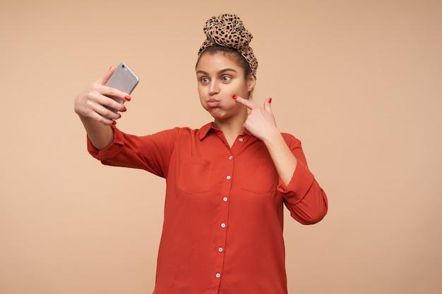 Lustiger schuss der jungen fröhlichen braunhaarigen dame, die ihre wangen aufbläst, während sie täuscht und selfie mit ihrem smartphone macht, lokalisiert über beige wand
