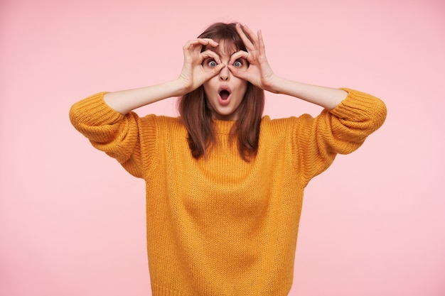 Lustiger schuss der reizenden jungen dunkelhaarigen dame, die mit großen augen und geöffnetem mund schaut und erhobene hände auf ihrem gesicht hält, während sie über rosa wand posiert