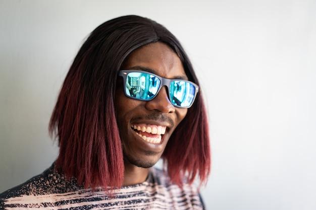 Lustiger schwarzer junge mit langen haaren und sonnenbrille lachen
