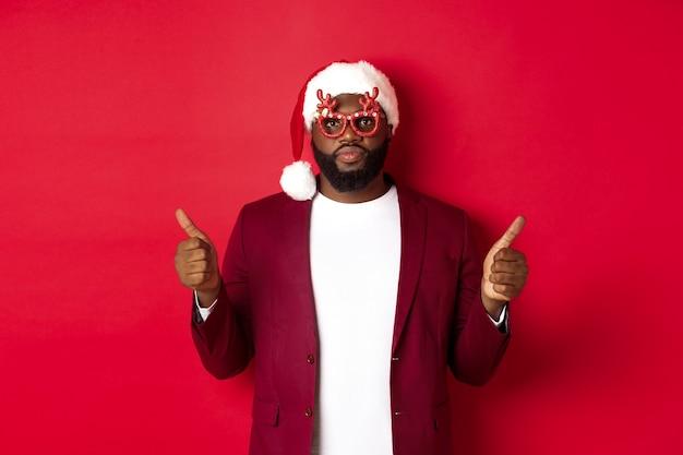 Lustiger schwarzer mann, der neujahr feiert, eine partybrille und eine weihnachtsmütze trägt, daumen nach oben zeigt, genehmigt und mag, über rotem hintergrund stehend