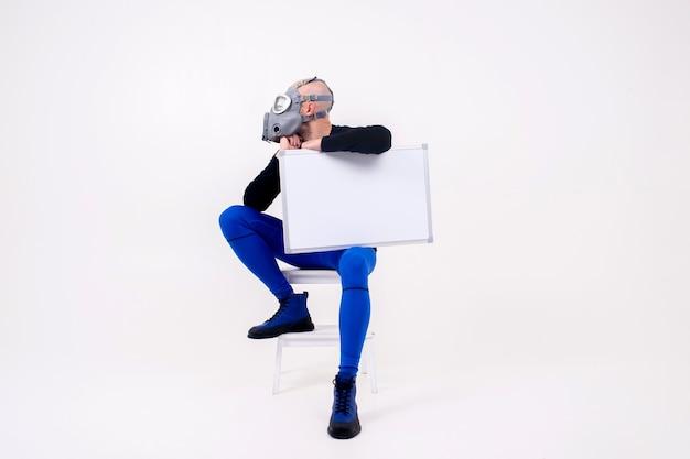 Lustiger seltsamer mann im atemschutzgerät, der auf trittleiter mit einem markierungsbrett über weißer wand sitzt
