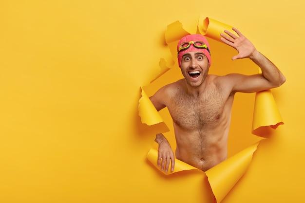 Lustiger sportler mann hat starken nackten körper, wellen mit der handfläche, sieht mit überglücklichem gesichtsausdruck aus