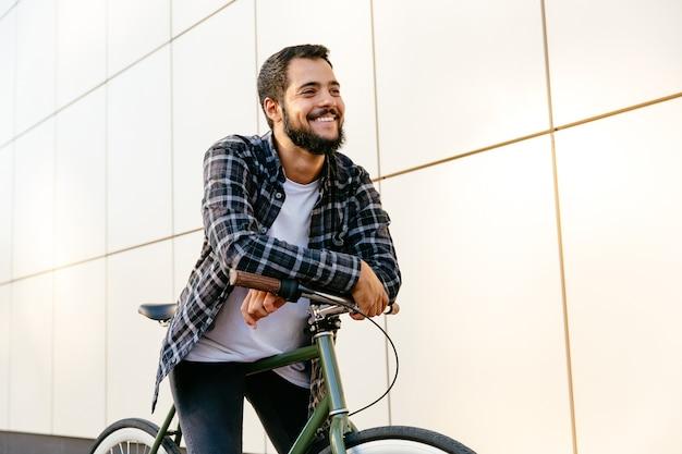 Lustiger stilvoller mann, der auf dem fahrrad, die freizeit draußen genießend sitzt.