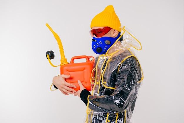 Lustiger stilvoller seltsamer mann in der maske mit dem wassertopf, der über weißer wand aufwirft