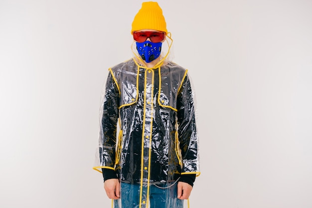 Lustiger stilvoller seltsamer mann in der maske und im regenmantel