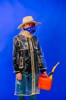 Lustiger stilvoller seltsamer mann in der maske und im strohhut mit dem roten wassertopf, der über blauem hintergrund aufwirft