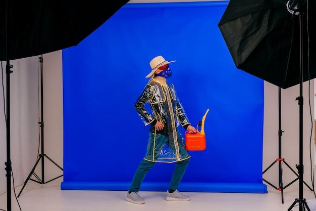 Lustiger stilvoller seltsamer mann in der maske und im strohhut mit dem roten wassertopf, der über der blauen wand aufwirft