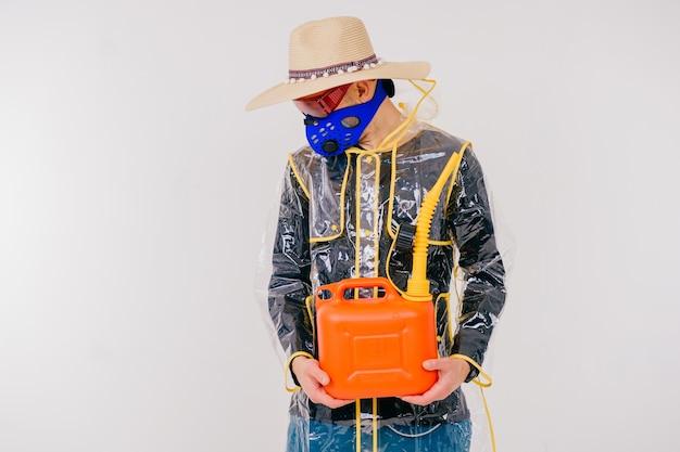 Lustiger stilvoller seltsamer mann in der maske und im strohhut mit dem wassertopf, der über weißer wand aufwirft