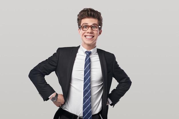 Lustiger stolzer, selbstbewusster junger mann in elegantem anzug und nerdiger brille, der die hände an der taille hält und in die kamera schaut, mit einem lächeln auf weißem hintergrund