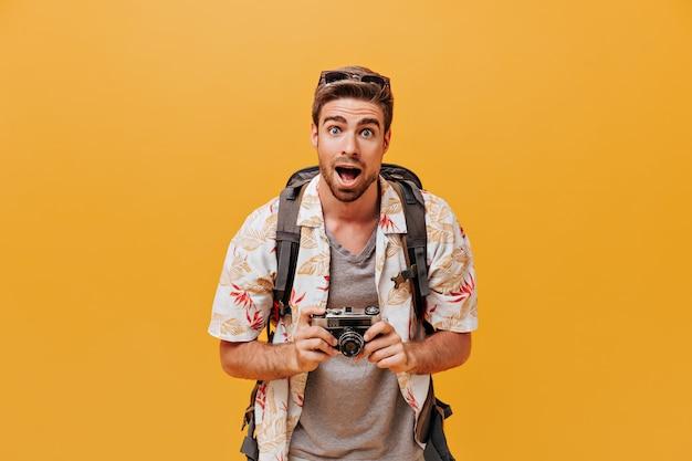 Lustiger tourist mit blauen augen in sonnenbrille, modischem sommerhemd und grauem kariertem t-shirt mit blick in die kamera auf oranger wand camera