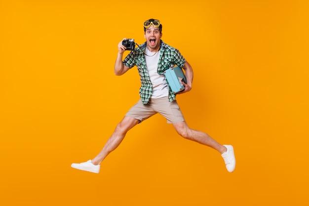 Lustiger touristischer kerl im sommeroutfit, das retro-kamera und blauen koffer hält. mann in der tauchmaske, die auf orange raum springt.