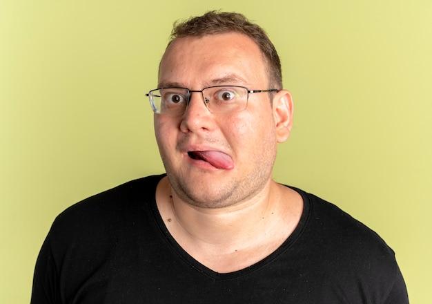 Lustiger übergewichtiger mann in der brille, die das schwarze t-shirt trägt, das zunge über licht herausragt