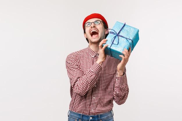 Lustiger und aufgeregter hipster-typ des taillenporträts, der geburtstag feiert, geschenk erhält und vor aufregung und jubel schreit, schaut auf, hält eingewickeltes geschenk nahe ohr, weiße wand