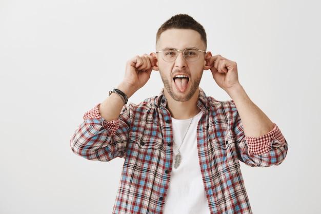 Lustiger und dummer junger mann mit brille, die aufwirft
