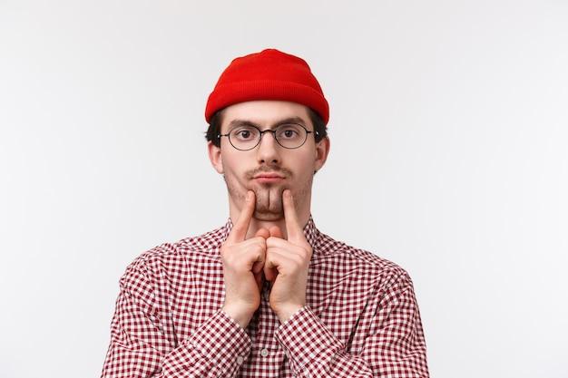 Lustiger und niedlicher bärtiger kaukasischer kerl in gläsern und roter mütze, quetschbacken, um doppelkinn zu machen