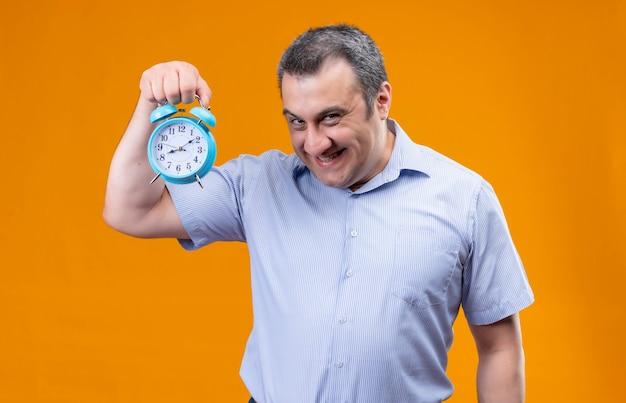 Lustiger und positiver mann im blau gestreiften hemd, das blauen wecker hält und zeit beim stehen zeigt