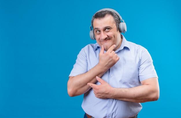 Lustiger und positiver mann mittleren alters im blau gestreiften hemd in den kopfhörern, die denken und hand auf kinn auf einem blauen raum legen