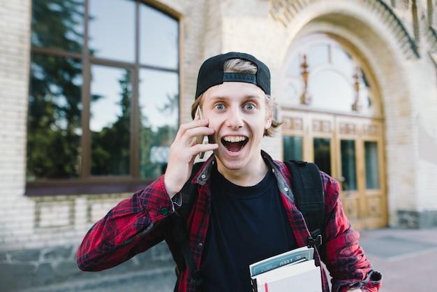 Lustiger und sehr emotionaler junger mann spricht telefonisch vor dem hintergrund der architektur.