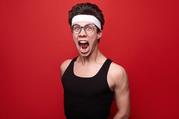 Lustiger verrückter junger dünner kerl in sportoutfit und brille, der während des fitnesstrainings vor rotem hintergrund eine grimasse verzieht und laut schreit