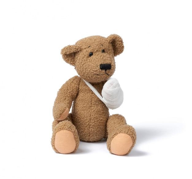 Lustiger vintage brauner lockiger teddybär mit zurückgespulter pfote mit weißem mullverband