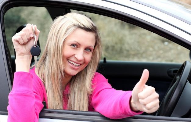 Lustiger weiblicher fahrer, der einen schlüssel zeigt, nachdem er ein neues auto bying gemacht hat