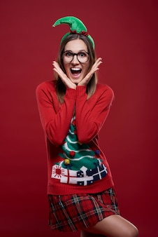 Lustiger weiblicher nerd gekleidet in weihnachtskleidung