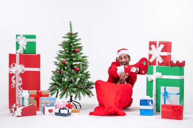 Lustiger weihnachtsmann, der auf dem boden sitzt und weihnachtssocke nahe geschenken und geschmücktem neujahrsbaum auf weißem hintergrund trägt