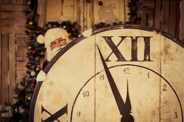 Lustiger weihnachtsmann, der große uhr hält. neujahrsferienkonzept
